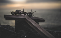 wooden cross and crown of thorns on a rock at sunset