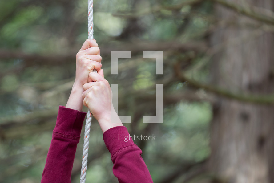 Hands hanging from a rope.