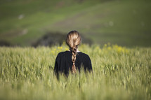 a woman standing in a field of wheat
