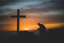 silhouette of a praying man and cross at sunset