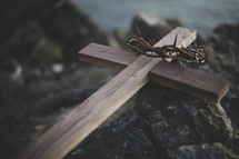 cross and crown of thorns on a rock