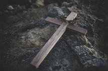 wooden cross and crown of thorns on a rock