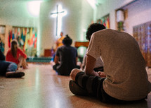 teens sitting on the floor during a worship service