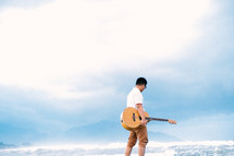 a man with a guitar on a beach