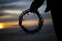 man holding a crown of thorns at sunset
