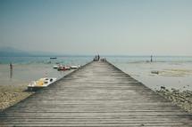 a wood pier on a beach