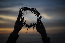 silhouette of a man holding up a crown of thorns at sunset