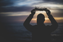 person holding up a crown of thorns at sunset