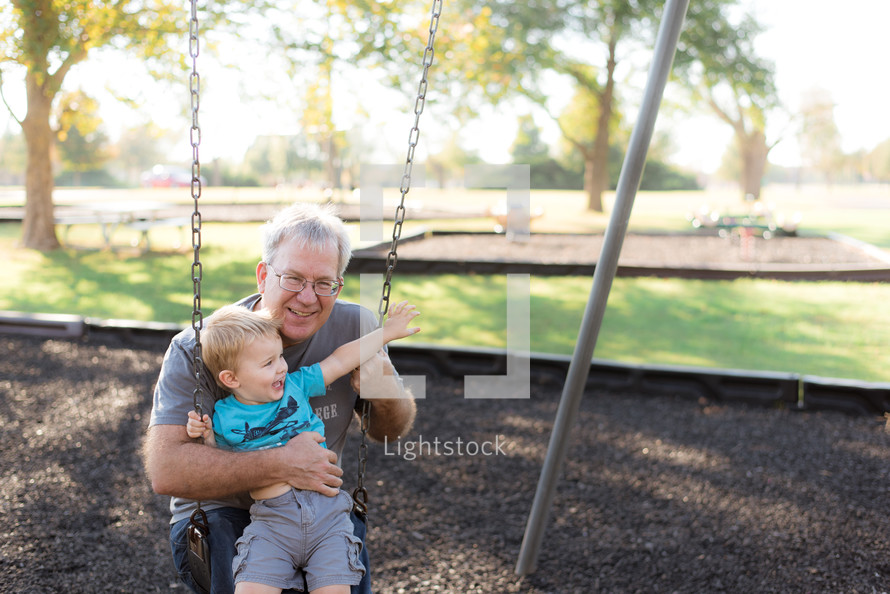 grandfather and grandson swinging on a swing