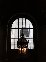 lamp hanging from a ceiling in front of a window in a cathedral