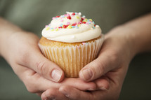 cupped hands holding a cupcake