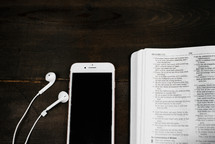 iPhone with earbuds and an open Bible