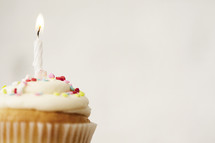 cupcake and candles against a white background