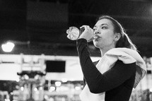 a woman drinking water in the gym