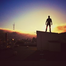 Man on rooftop at sunset