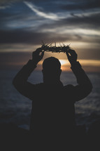 man holding up a crown of thorns at sunset