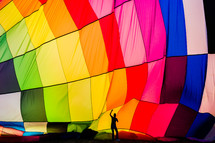 Man in front of a rainbow colored hot air balloon perspective, scale
