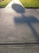 shadow of a stop sign on a sidewalk
