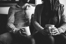 A young couple sitting on a couch drinking coffee
