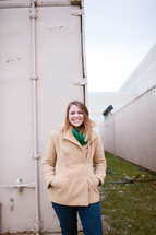 woman in coat standing in front of a storage bin