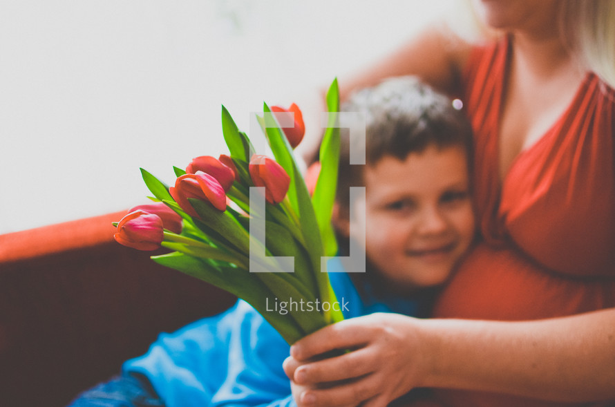 a boy giving his mother flowers for mother's day