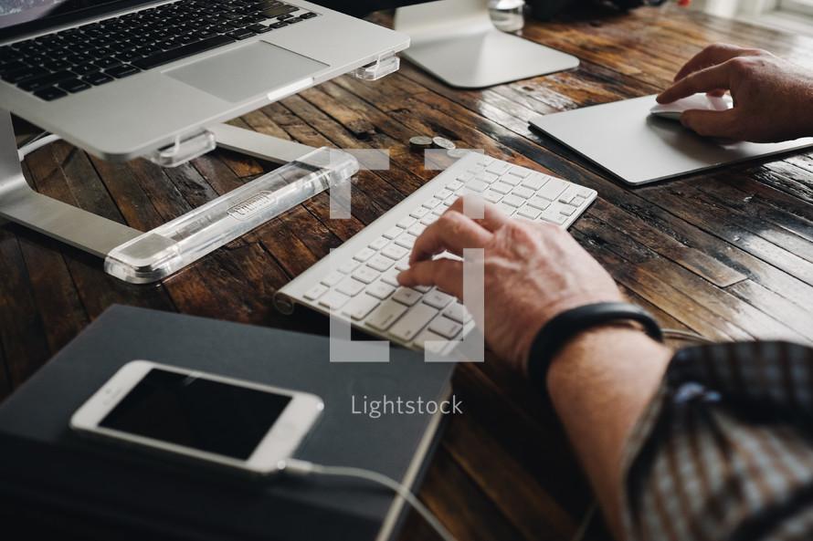man typing, laptop, keyboard, earbuds, Book, coins, tablet