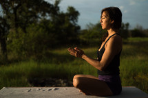 a woman doing yoga and meditating outdoors