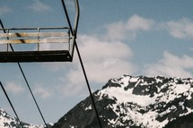 ski lift and a snow capped mountain peak