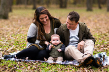portrait of a young family sitting on a blanket in the grass