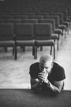 Man leaning on stage with eyes closed, head on hands in prayer.
