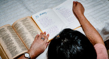 young woman reading a Bible and taking notes