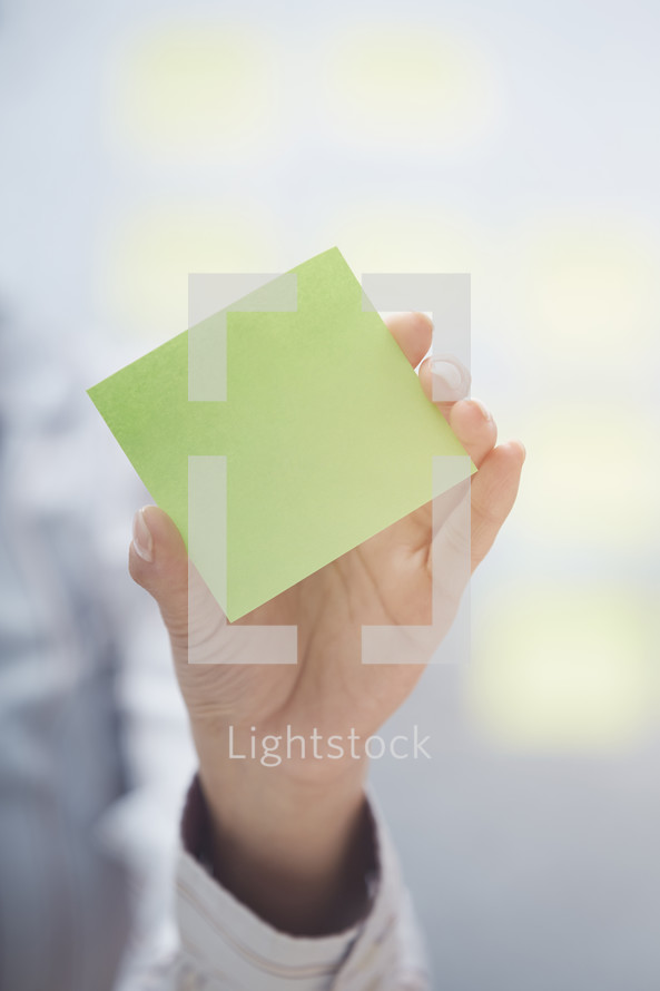woman holding a pad of sticky notes