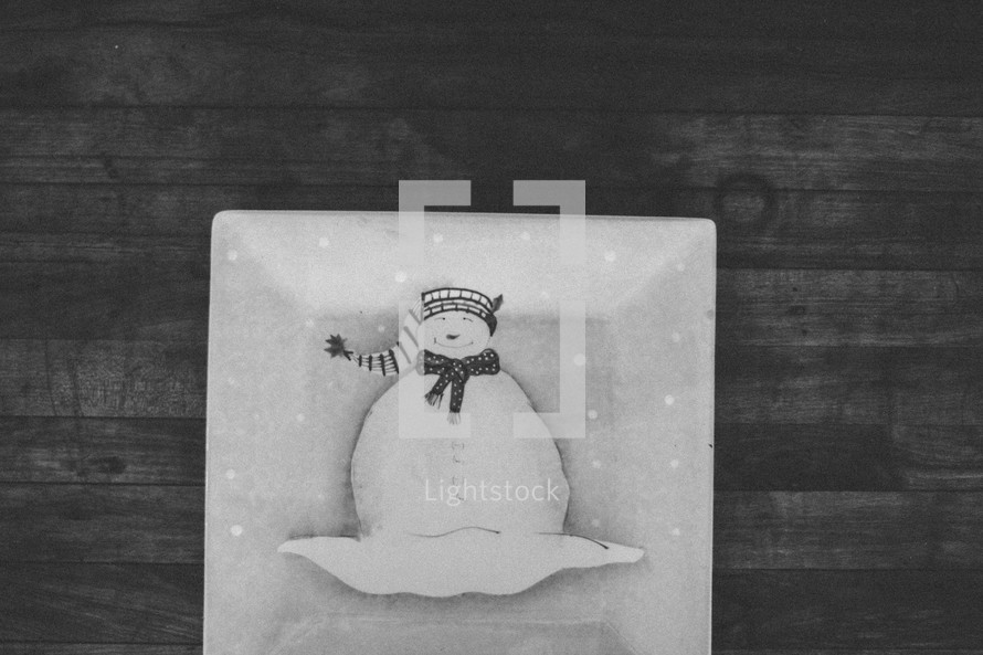 A white snowman plate on wood