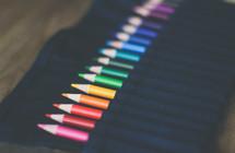 colored pencils in a black apron