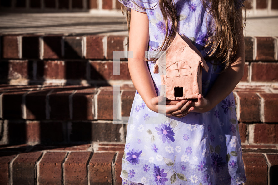 Girl holding clay model of a home in hands, brick steps in background; As for me and my house, we will serve the Lord  (Joshua 24:15)