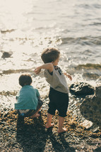 children through stones on a beach