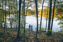 a couple standing by a lakeshore under a forest canopy