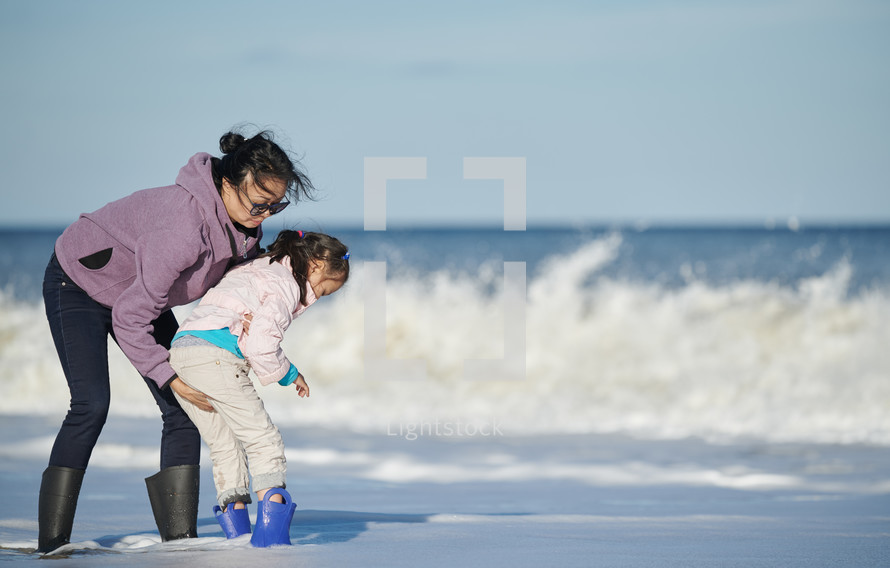mother and daughter playing on a beach