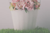 pink roses in a white pail on grass