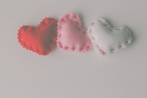 Felt hearts with stitching around the edges.