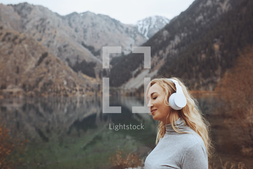 Woman wearing wireless headphones at the mountain lake