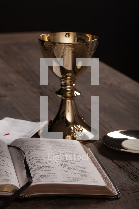 A golden communion goblet, communion wafer and an open Bible.
