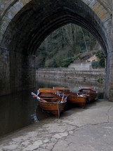 paddle boats in water under a bridge
