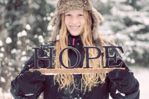 "A girl in winter clothes holding a sign that says, ""Hope,"""