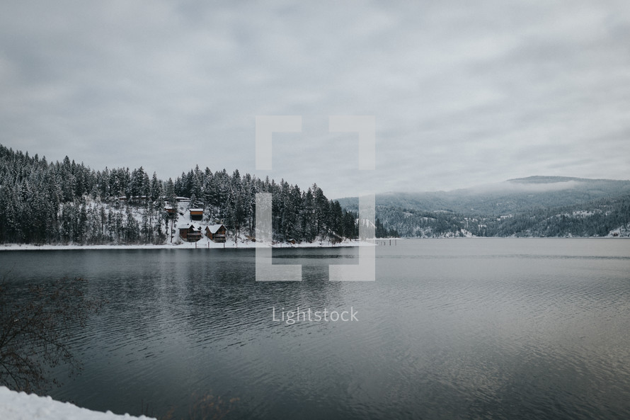 cabins on a snowy hill by a lake shore