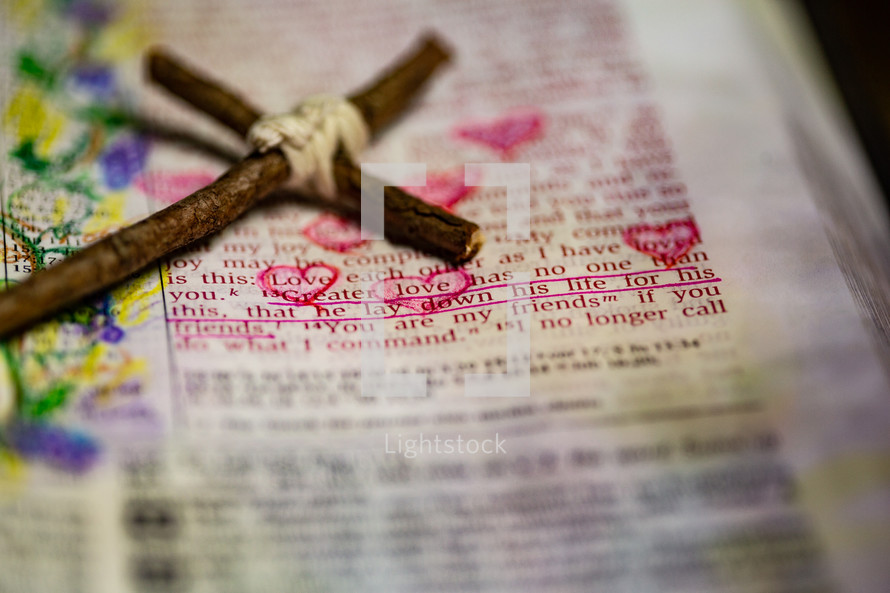 """Rustic handmade cross laying by John 15:13 scripture accompanied by hand-drawn doodles in Bible """"Greater love has no one than this, that one lay down his life for his friends."""""""