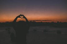 silhouette of a woman making a heart shape with her hands