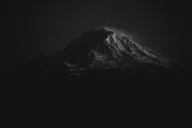 A snow capped mountain peak at night