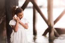a girl listening to a seashell on a beach