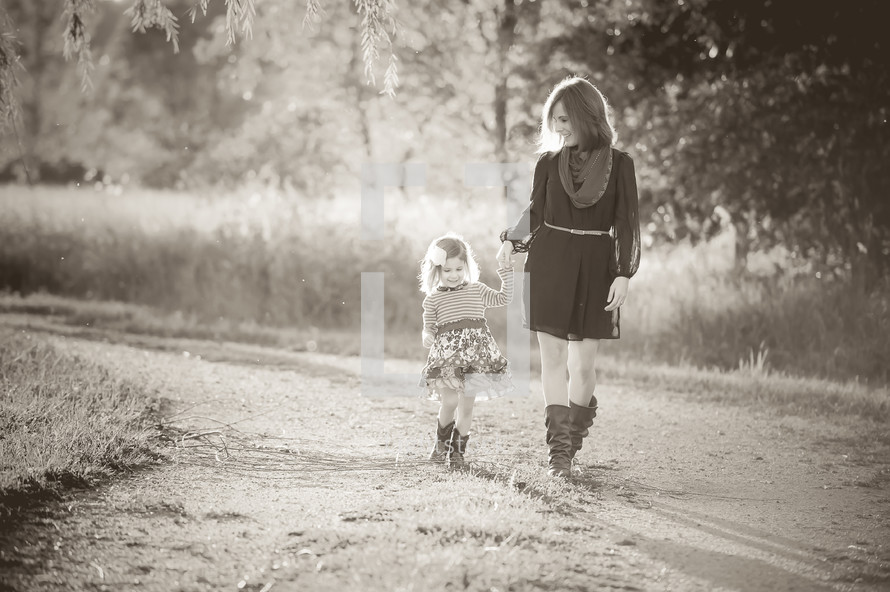 A mother and daughter holding hands walking outdoors.